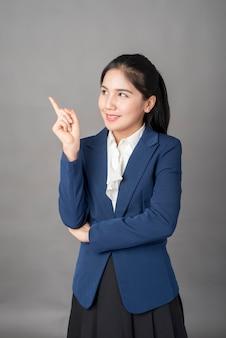 Porträt der intelligenten geschäftsfrau in der blauen klage zeigend mit ihrem finger