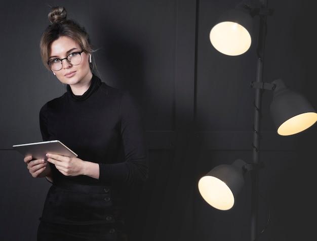 Porträt der intelligenten jungen frau, die im büro aufwirft