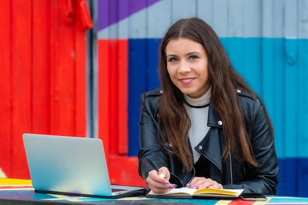 Porträt der intelligenten jungen frau mit notizbuch, das am laptop am kaffeehaus im freien arbeitet