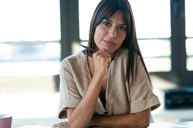 Porträt der intelligenten schönen jungen geschäftsfrau, die die kamera betrachtet, die im büro sitzt.