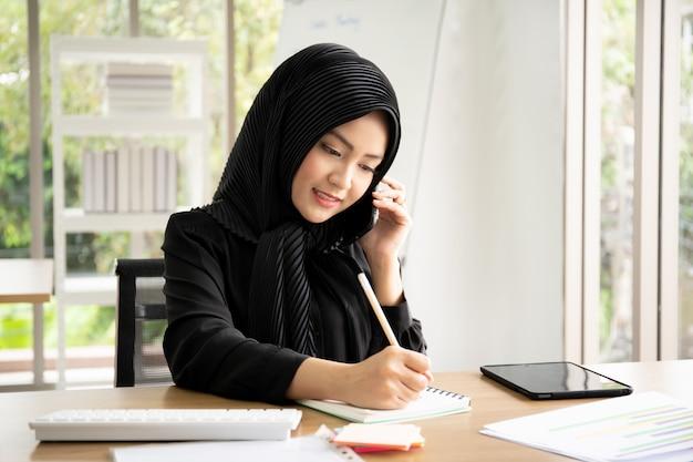 Porträt der intelligenten schönen muslimischen geschäftsfrau, die im büro arbeitet