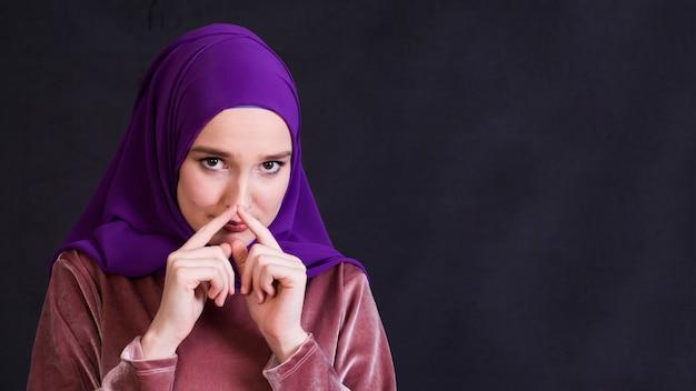 Porträt der islamischen frau tragendes hijab, das kamera betrachtet