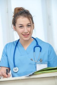 Porträt der jungekrankenschwester in der blauen uniform