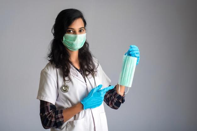 Porträt der jungen ärztin, die geöffnete medizinische maske zeigt. quarantänemaßnahmen und lebensrettendes konzept