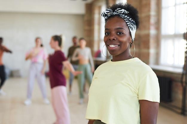 Porträt der jungen afrikanischen frau, die an der kamera während des trainings im tanzstudio lächelt