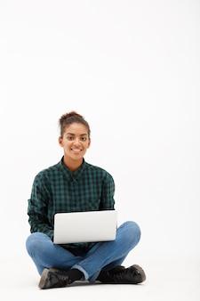 Porträt der jungen afrikanischen frau mit laptop auf weiß