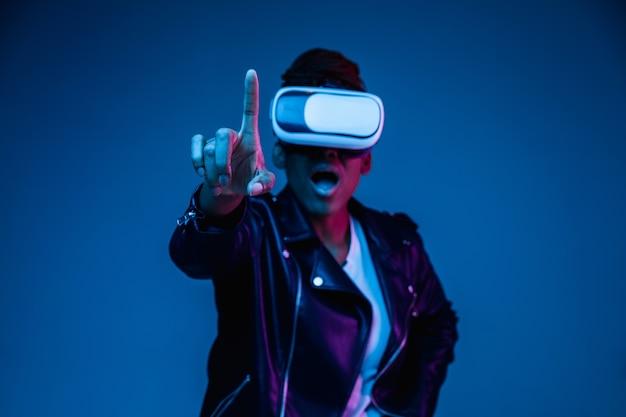 Porträt der jungen afroamerikanerfrau, die in vr-brille im neonlicht auf blauem hintergrund spielt