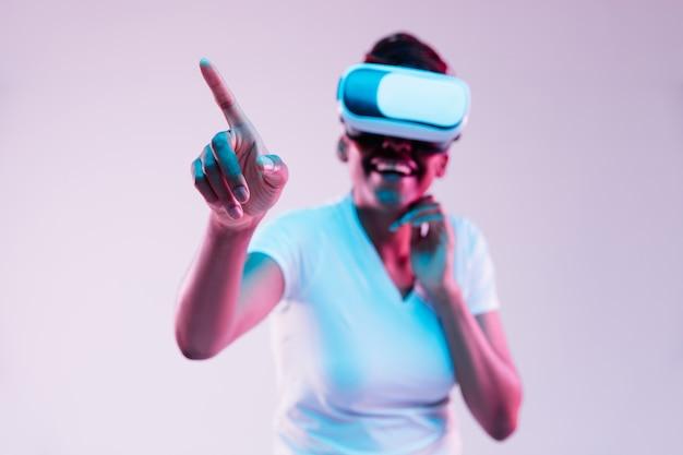 Porträt der jungen afroamerikanerfrau, die in vr-brille im neonlicht auf gradientenhintergrund spielt. konzept menschlicher emotionen, gesichtsausdruck, moderner geräte und technologien. berührt die leere leiste.