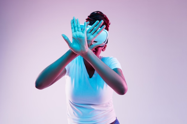 Porträt der jungen afroamerikanerfrau, die in vr-brille im neonlicht auf gradientenhintergrund spielt