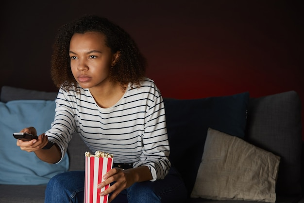 Porträt der jungen afroamerikanerin, die zu hause fernsieht und fernbedienung hält, während auf couch im dunklen raum sitzend