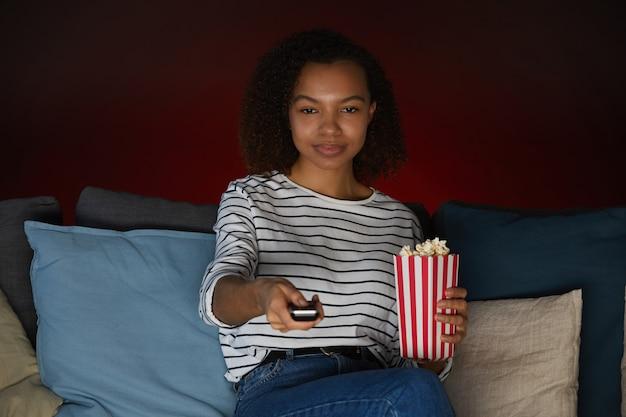 Porträt der jungen afroamerikanerin, die zu hause fernsieht und popcorn hält, während sie auf couch in dunklem raum sitzt