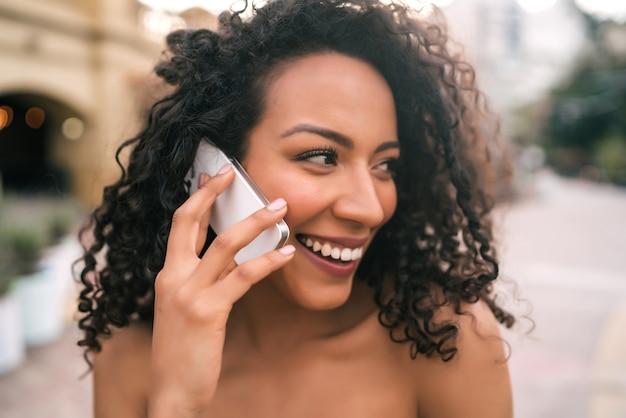 Porträt der jungen afroamerikanischen lateinamerikanischen frau, die am telefon draußen in der straße spricht. technologiekonzept.