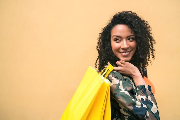 Porträt der jungen afroamerikanischen lateinamerikanischen frau, die einkaufstaschen gegen gelben hintergrund hält. shop- und lifestyle-konzept.
