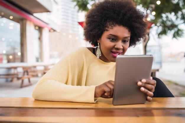 Porträt der jungen afroamerikanischen lateinamerikanischen frau, die ihr digitales tablett beim sitzen am coffeeshop verwendet. technologiekonzept.