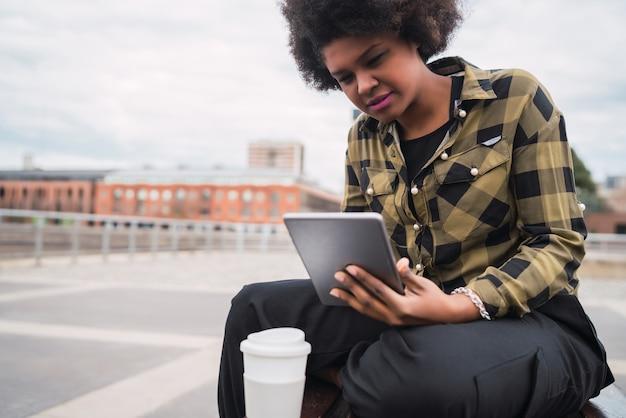 Porträt der jungen afroamerikanischen lateinamerikanischen frau, die ihr digitales tablett beim sitzen auf einer bank im freien verwendet. technologiekonzept.