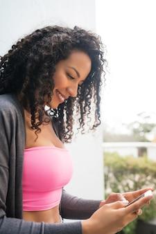 Porträt der jungen afroamerikanischen lateinamerikanischen frau, die ihr handy benutzt und nachrichten sendet. kommunikationskonzept.