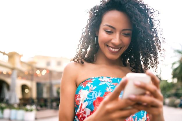 Porträt der jungen afroamerikanischen lateinamerikanischen frau, die ihr handy draußen in der straße benutzt. technologiekonzept.