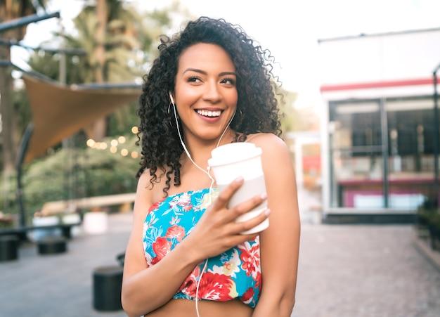 Porträt der jungen afroamerikanischen lateinamerikanischen frau, die musik mit kopfhörern hört, während eine tasse kaffee draußen in der straße hält.