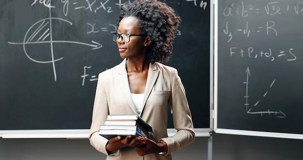 Porträt der jungen afroamerikanischen lehrerin in den gläsern, die kamera im klassenzimmer betrachten und lehrbücher halten. tafel mit formeln auf hintergrund. schulkonzept. bücher in frauenhänden.