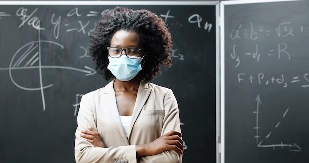 Porträt der jungen afroamerikanischen lehrerin in den gläsern und in der medizinischen maske, die kamera betrachten und hände im klassenzimmer kreuzen. tafel mit mathematischen formeln auf hintergrund. pandemie-schulbildung.