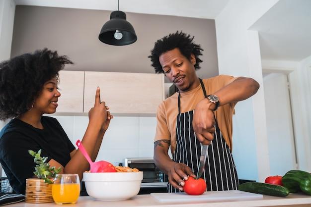 Porträt der jungen afrofrau, die foto ihres mannes macht, während er das abendessen zubereitet. beziehungs-, koch- und lifestyle-konzept.