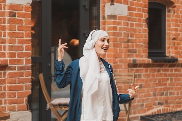 Porträt der jungen arabischen muslimischen frau, die musik mit kopfhörer hört und feminismusfrau tanzt