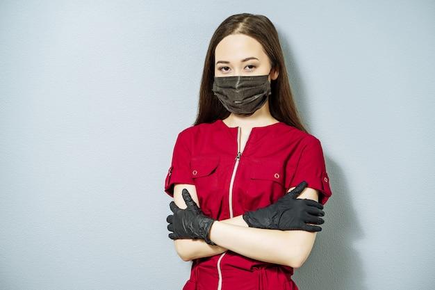 Porträt der jungen asiatin in der medizinischen uniform und in der schwarzen maske und in den handschuhen auf grauem hintergrund