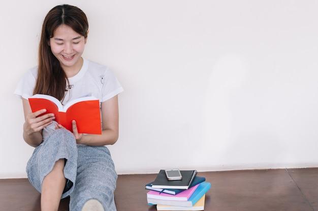 Porträt der jungen asiatin sitzend ein buch auf boden lesend.