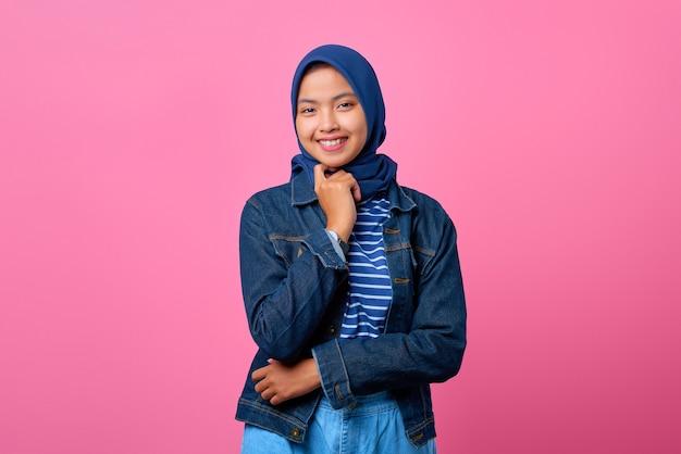 Porträt der jungen asiatischen frau des glücks, die mit verschränktem arm und hand am kinn selbstbewusst aussieht