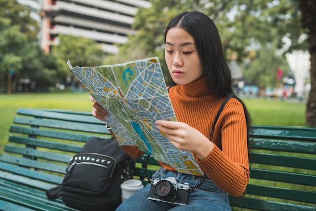 Porträt der jungen asiatischen frau, die auf bank im park sitzt und eine karte betrachtet. reisekonzept. draußen.