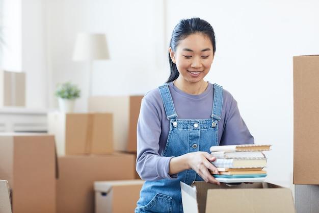 Porträt der jungen asiatischen frau, die bücher zu pappkartons packt und glücklich aufgeregt für den umzug in neues haus oder wohnheim lächelt