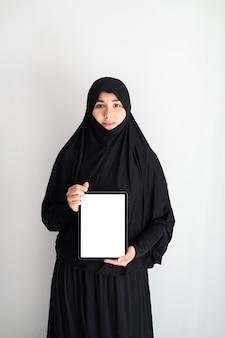 Porträt der jungen asiatischen frau, die hijab trägt und zu hause mit tablette arbeitet