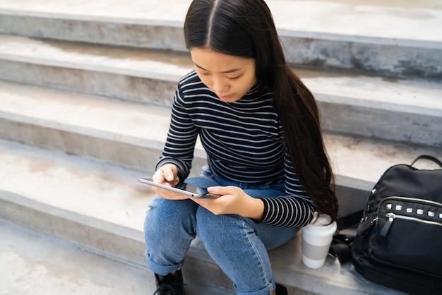 Porträt der jungen asiatischen frau, die ihr digitales tablett beim sitzen an der treppe im freien verwendet. technologiekonzept.