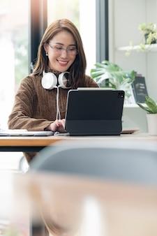 Porträt der jungen asiatischen frau, die im heimbüro mit glück, erfolgreichem konzept arbeitet.