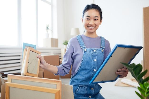 Porträt der jungen asiatischen frau, die kisten packt und für den umzug in ein neues haus oder eine neue wohnung aufgeregt lächelt