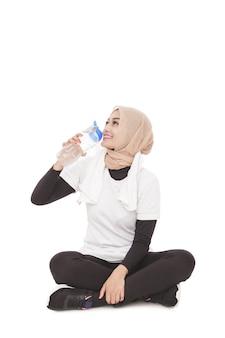 Porträt der jungen asiatischen frau, die mineralwasser während der pause nach dem training trinkt