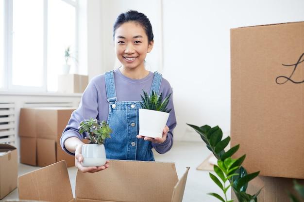 Porträt der jungen asiatischen frau, die pflanzen zu pappkartons verpackt, die zu neuem haus oder zu wohnung ziehen