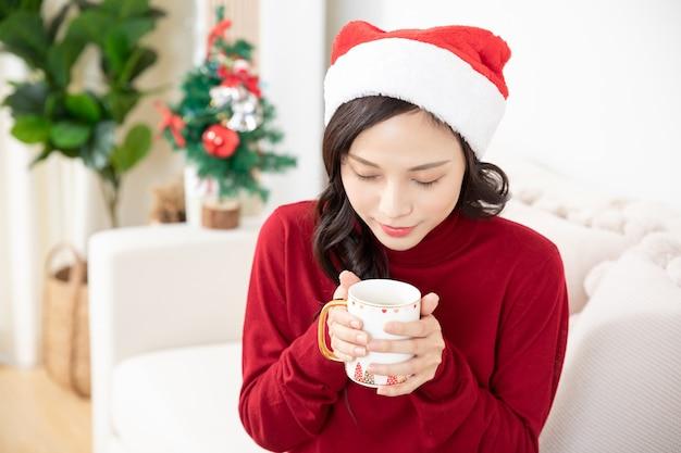 Porträt der jungen asiatischen frau, die weihnachten und neujahr zu hause feiert