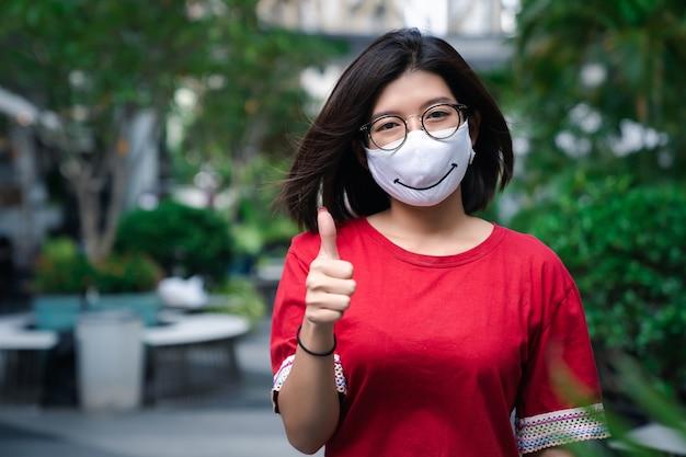Porträt der jungen asiatischen frau lächelnd tragen brillen und gesichtsmaske beim gehen im freien mit daumen nach oben geste, gesundheitswesen