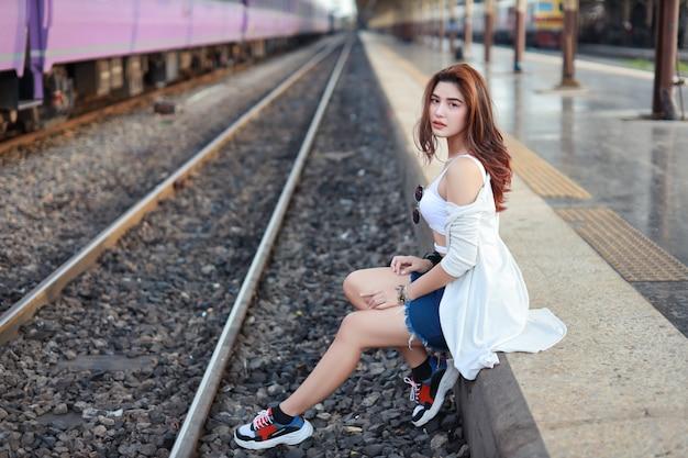 Porträt der jungen asiatischen frau, langes haar im weißen kleid, das kamera bei der aufwartung in bahnstation mit schönheitsgesicht sitzt und betrachtet