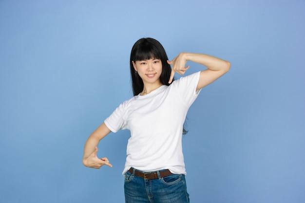 Porträt der jungen asiatischen frau lokalisiert auf blauem studioraum