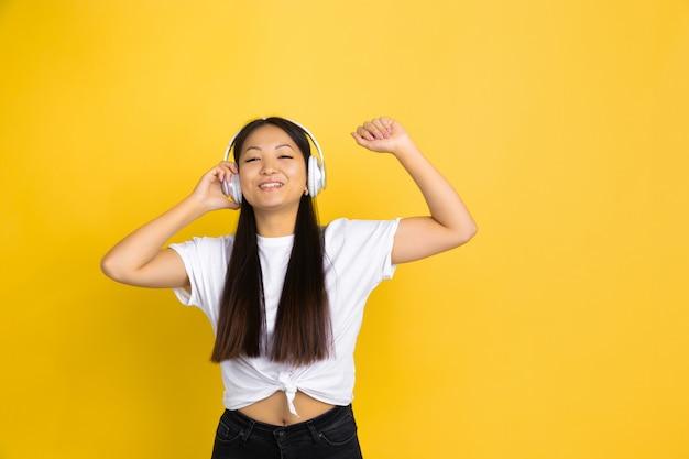 Porträt der jungen asiatischen frau lokalisiert auf gelber wand