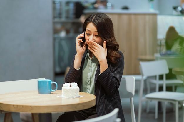 Porträt der jungen asiatischen geschäftsfrau, die kaffee trinkt, sahnetorte isst und telefon benutzt