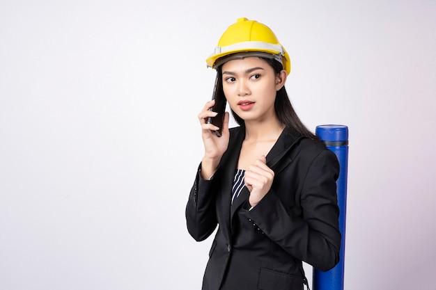 Porträt der jungen asiatischen geschäftsfrau in der klage unter verwendung des mobiles