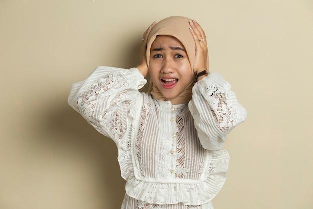 Porträt der jungen asiatischen muslimischen frau, die hijab a trägt, bedeckt ihre ohren