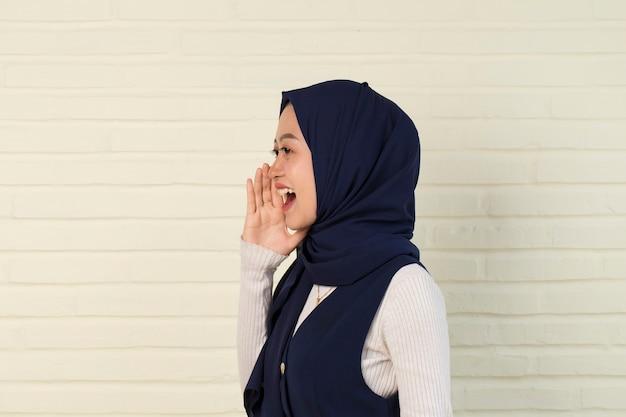 Porträt der jungen asiatischen muslimischen frau, die hijab schreiend und schreiend trägt