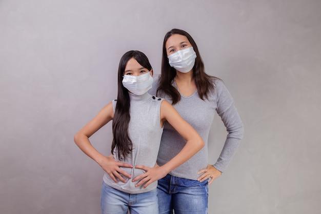 Porträt der jungen asiatischen mutter mit ihrer kindertochter, die maske trägt. mutter und tochter tragen maske zum schutz von covid 19, quarantäne. bleiben sie zu hause konzept.