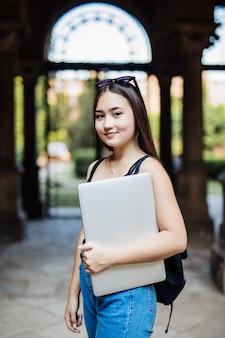 Porträt der jungen asiatischen studentin, die einen laptop oder ein tablet in der intelligenten und glücklichen pose an der universität oder im college verwendet