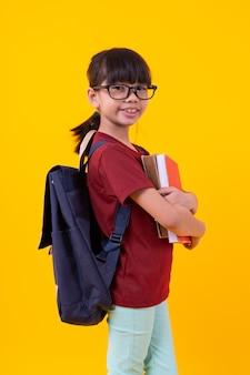 Porträt der jungen asiatischen studentin, welche die bücher zeigen oben auf gelb hält