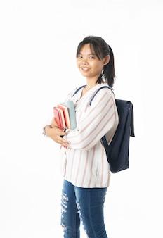 Porträt der jungen asiatischen thailändischen studentin, die buch lokalisiert auf weißem hintergrund hält